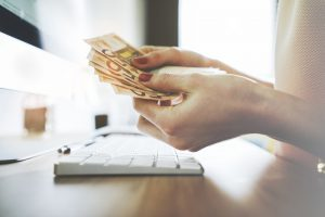 Frau zählt Geldscheine vor dem Rechner.